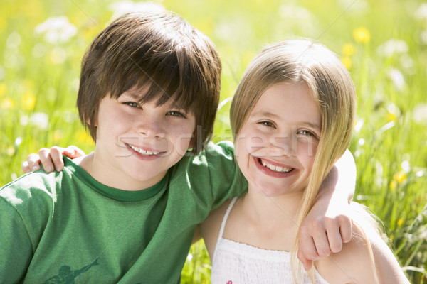 Two young children sitting outdoors arm in arm smiling Stock photo © monkey_business