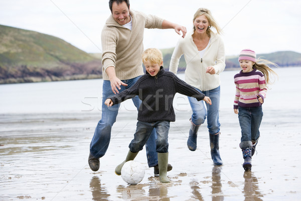 Stock photo: Family playing soccer at beach smiling