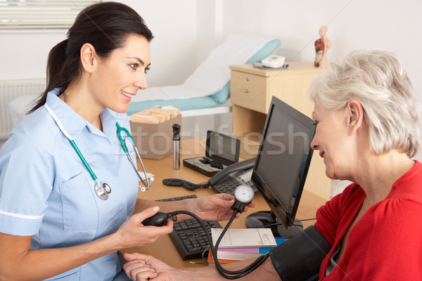 British nurse taking senior woman's blood pressure Stock photo © monkey_business