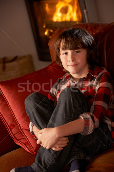 Young Boy Sitting On Sofa By Cosy Log Fire Stock photo © monkey_business