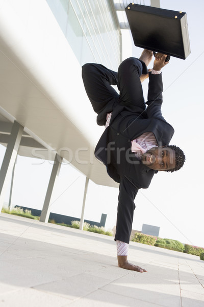Businessman outdoors by building standing on one hand smiling Stock photo © monkey_business
