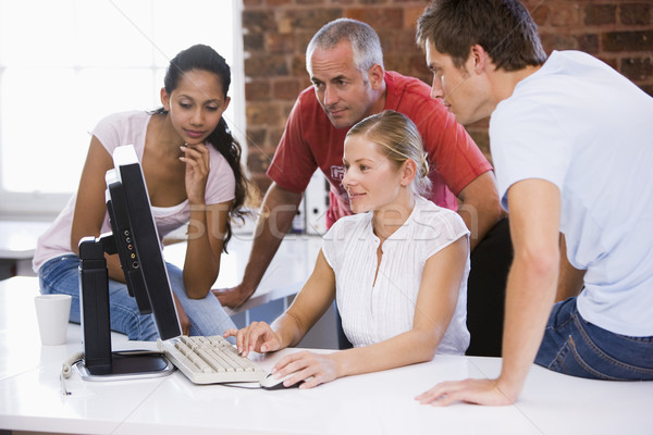 Stock photo: Four businesspeople in office space looking at computer smiling