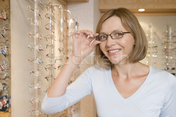 Woman trying on eyeglasses at optometrists smiling Stock photo © monkey_business