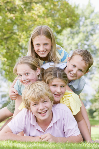 Five young friends piled on each other outdoors smiling Stock photo © monkey_business