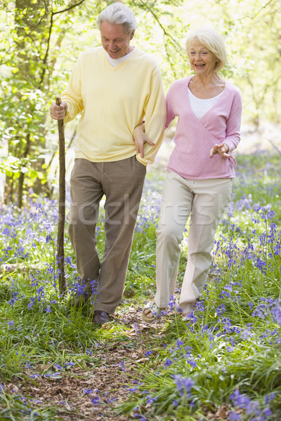 Couple walking outdoors with walking stick smiling Stock photo © monkey_business