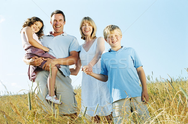 Family standing outdoors holding hands smiling Stock photo © monkey_business