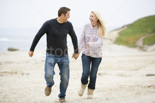 Couple running at beach holding hands smiling Stock photo © monkey_business