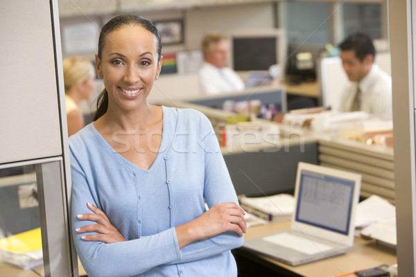 Businesswoman standing in cubicle smiling Stock photo © monkey_business