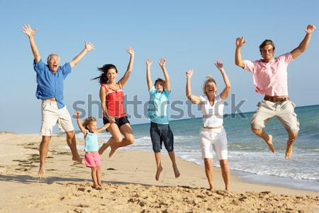 Stock photo: Portrait Of Three Generation Family On Beach Holiday Jumping In