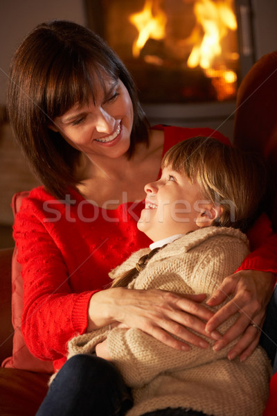 Mother And Daughter Relaxing On Sofa By Cosy Log Fire Stock photo © monkey_business
