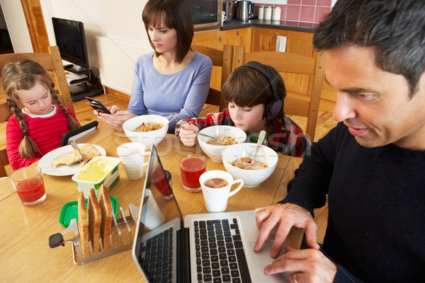 Family Using Gadgets Whilst Eating Breakfast Together In Kitchen Stock photo © monkey_business