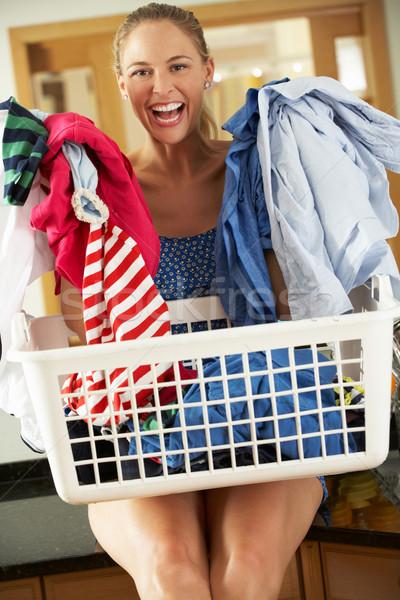 Woman Sitting On Kitchen Counter With Laundry Basket Stock photo © monkey_business