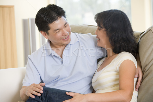 Couple relaxing in living room talking and smiling Stock photo © monkey_business