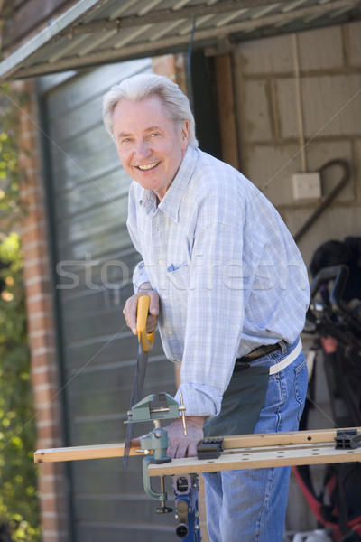 Man at shed sawing wood and smiling Stock photo © monkey_business