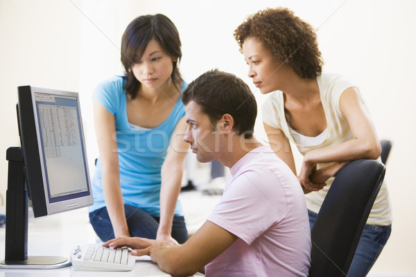 Three people sitting in computer room looking at monitor Stock photo © monkey_business