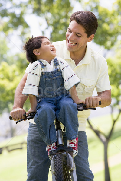 Man and young boy on a bike outdoors smiling Stock photo © monkey_business