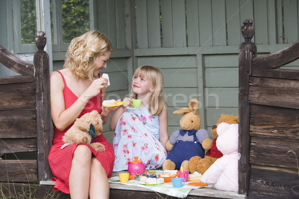 Woman and young girl in shed playing tea and smiling Stock photo © monkey_business