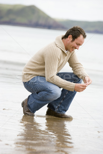 Man crouching on beach smiling Stock photo © monkey_business