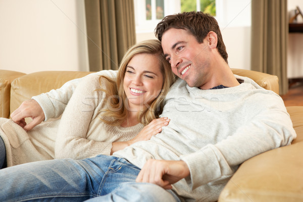 Stock photo: Young couple sitting and relaxing on sofa