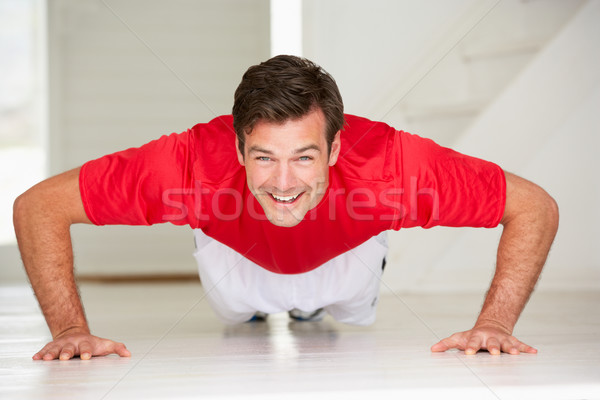 Man doing push-ups in home gym Stock photo © monkey_business