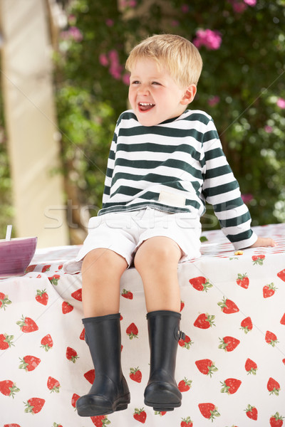 Young Boy Wearing Wellington Boots Sitting On Table Stock photo © monkey_business