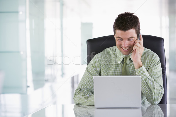 Businessman sitting in office using cellular phone and laptop Stock photo © monkey_business