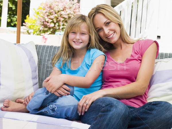 Woman and young girl sitting on patio smiling Stock photo © monkey_business