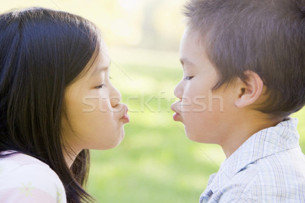 Brother and sister outdoors with eyes closed puckering up Stock photo © monkey_business