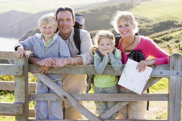 Stock photo: Family on cliffside path leaning on fence and smiling