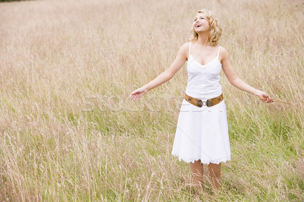Stock photo: Woman standing outdoors holding grass smiling