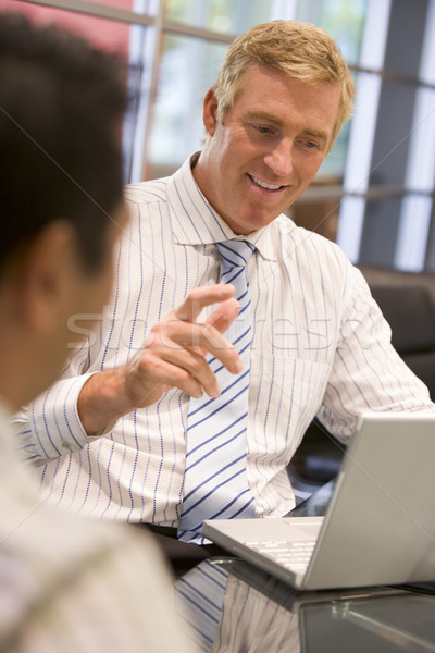 Two businessmen in boardroom with laptop talking Stock photo © monkey_business