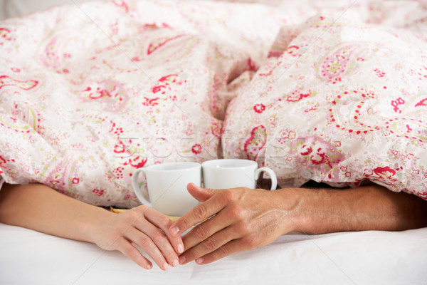 Romantic Couple Holding Hands Under Duvet In Bed Stock photo © monkey_business