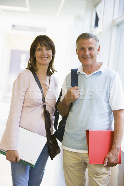 A man and woman with backpacks standing in a campus corridor Stock photo © monkey_business