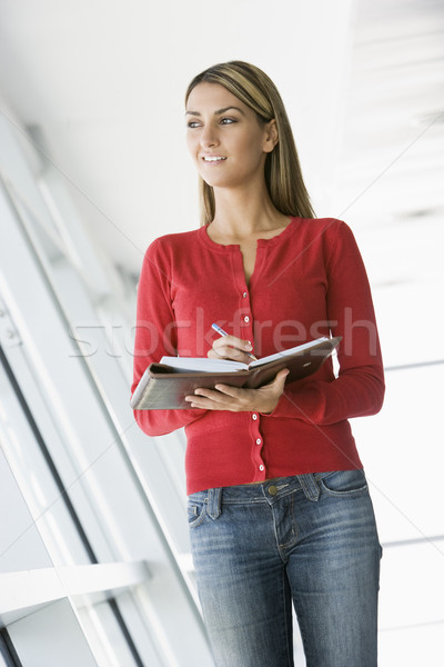Woman standing in corridor writing in personal organizer Stock photo © monkey_business