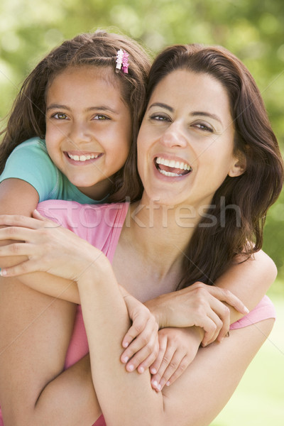 Woman and young girl embracing outdoors smiling Stock photo © monkey_business
