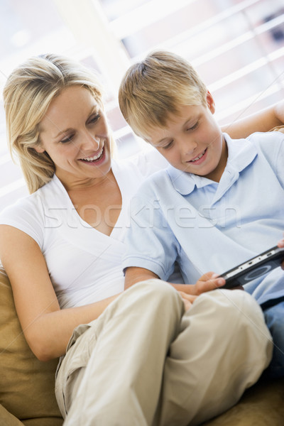 Woman and young boy in living room with handheld video game smil Stock photo © monkey_business