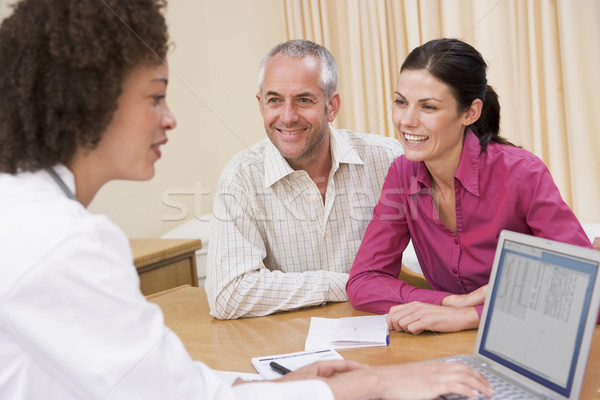 Doctor with laptop and couple in doctor's office smiling Stock photo © monkey_business