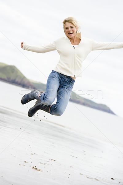 Сток-фото: женщину · прыжки · пляж · улыбающаяся · женщина · улыбаясь · морем
