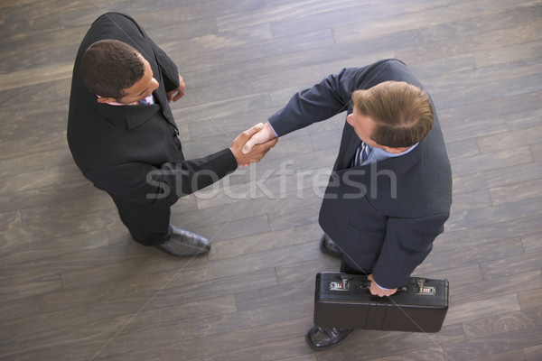 Two businessmen indoors shaking hands Stock photo © monkey_business