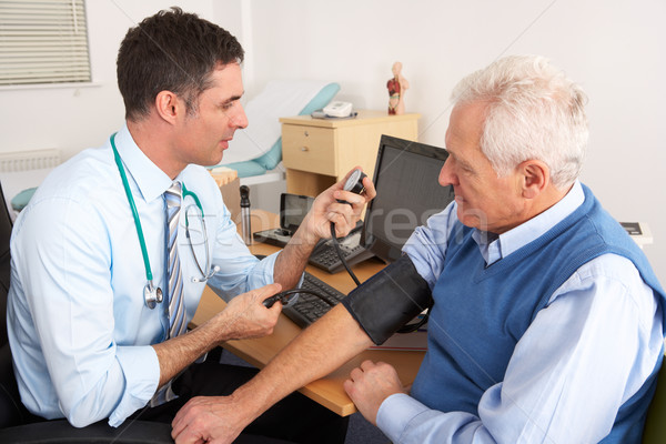British doctor taking senior man's blood pressure Stock photo © monkey_business