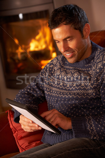 Middle Aged Man Using Tablet Computer By Cosy Log Fire Stock photo © monkey_business
