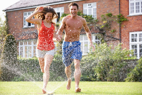 Couple Running Through Garden Sprinkler Stock photo © monkey_business