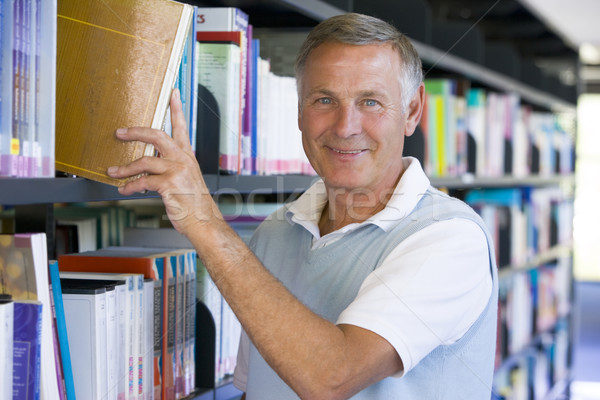 Senior man pulling a library book off shelf Stock photo © monkey_business