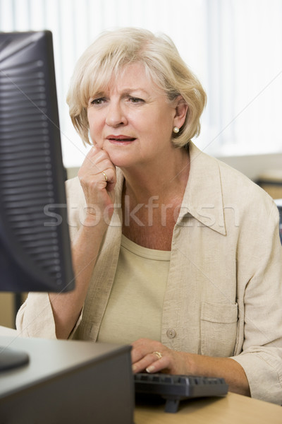 Confused woman frowning at computer monitor Stock photo © monkey_business