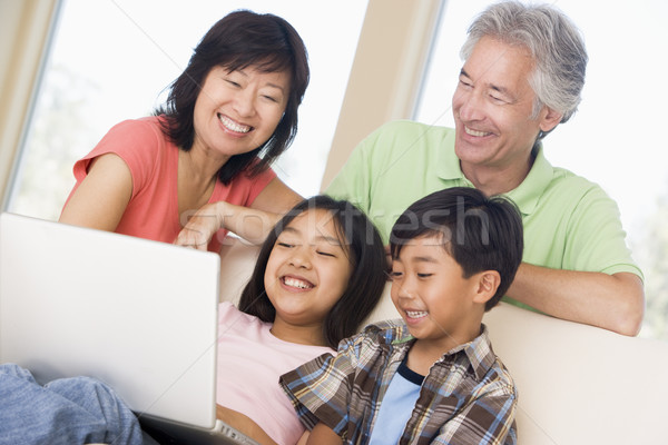 Couple with two young children in living room with laptop smilin Stock photo © monkey_business