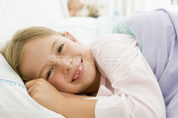 Jeune fille couché lit fille heureux enfant Photo stock © monkey_business