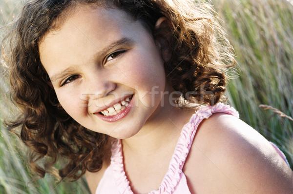 Jovem sessão ao ar livre sorridente menina grama Foto stock © monkey_business