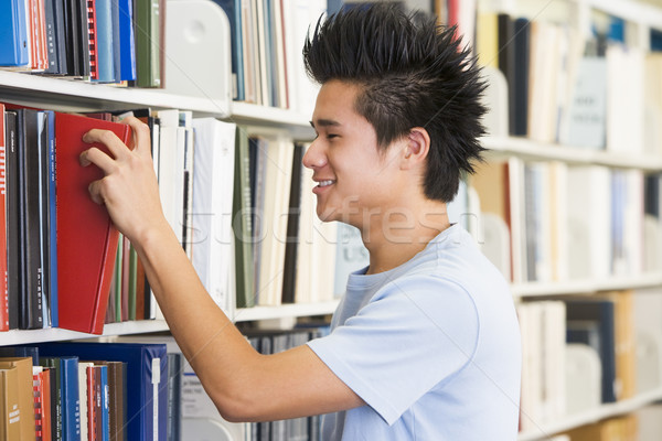 University student selecting book from library shelf Stock photo © monkey_business