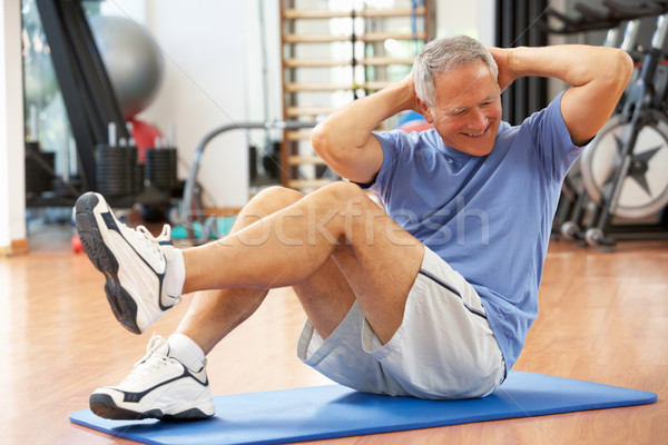 Senior Man Doing Sit Ups In Gym Stock photo © monkey_business