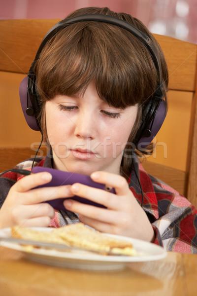 Garçon jouer main console de jeux manger déjeuner Photo stock © monkey_business